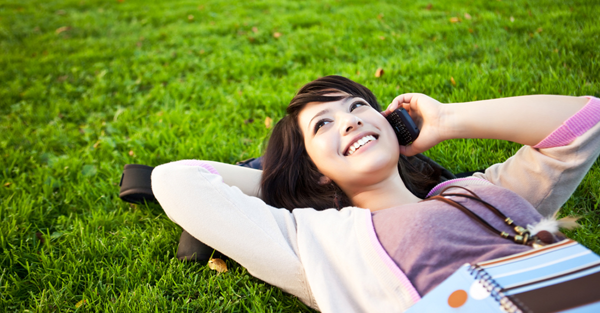 Smiling woman lying on a lawn, talking on the phone
